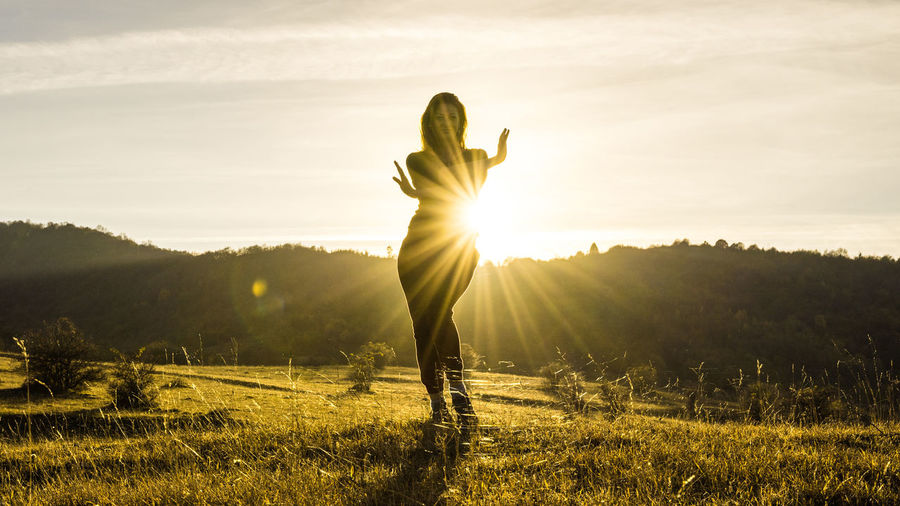 Woman standing on field against sky during sunset