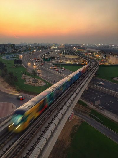 High angle view of train on bridge in city during sunset
