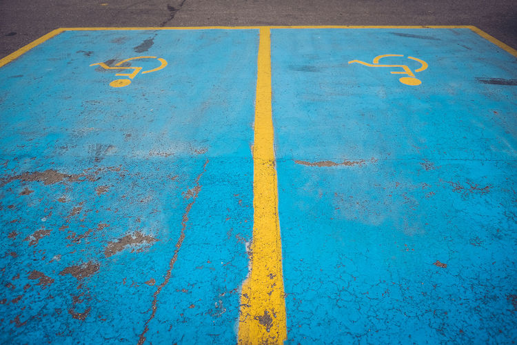High angle view of blue disabled road marking in parking lot