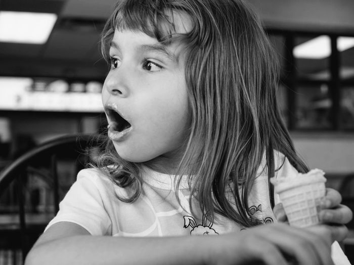 Cute surprised girl holding ice cream at restaurant