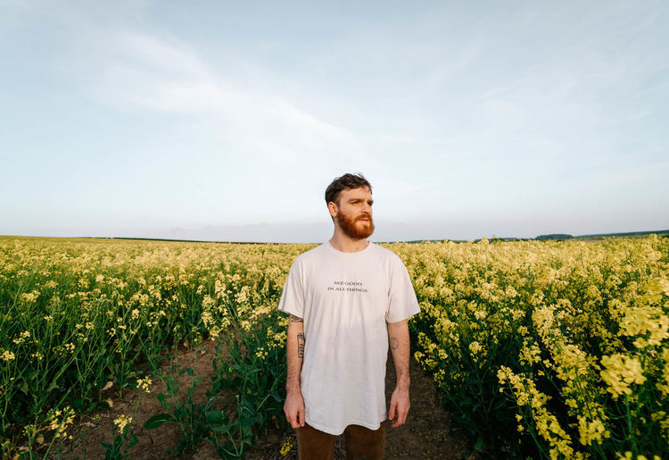 Young man looking away while standing amidst flowers against sky
