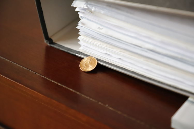 Close-up of coin by file on table