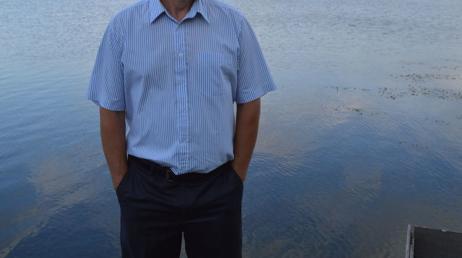 Midsection of man standing against lake
