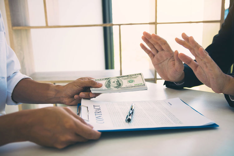Cropped hands of businessman bribing male coworker at desk in office
