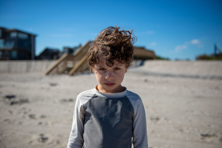 Portrait of angry boy standing on beach