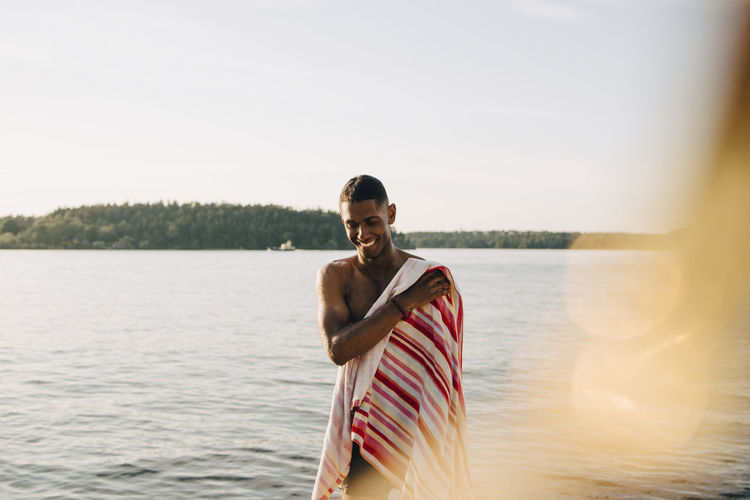 Portrait of young man standing in lake against sky