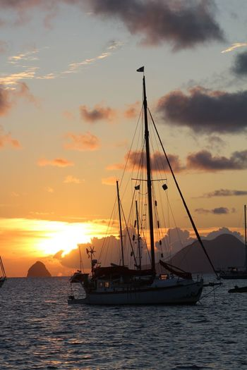 An anchored sailing boat anchored in a peaceful bay of Martinique at sunset. Sunset Water Transportation Sky Cloud - Sky Sea Sailboat Mast Sailing Orange Color No People Nature Scenics - Nature Beauty In Nature Waterfront Sailing Ship Outdoors Yacht Martinique
