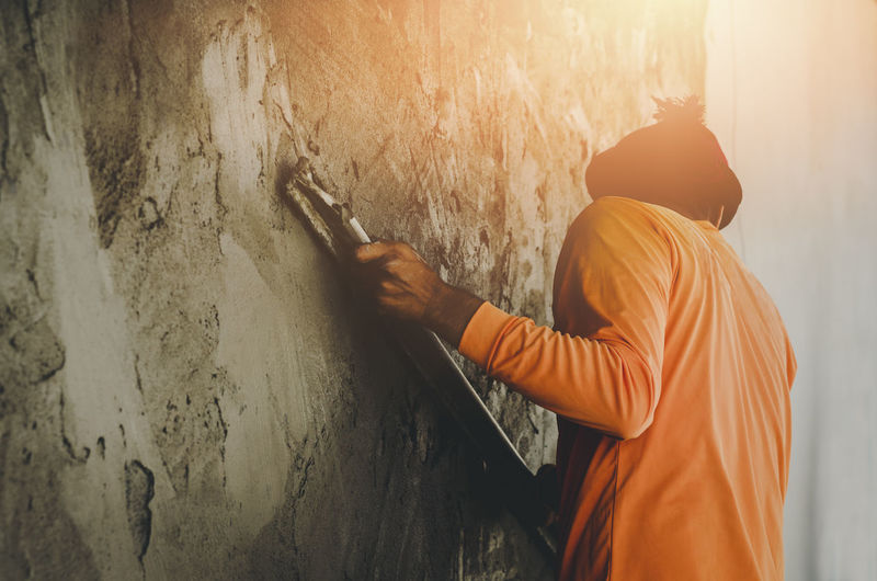 Rear View Of Man Fixing Wall