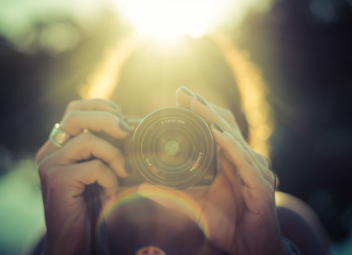Close-Up Of Woman Holding Camera On Sunny Day