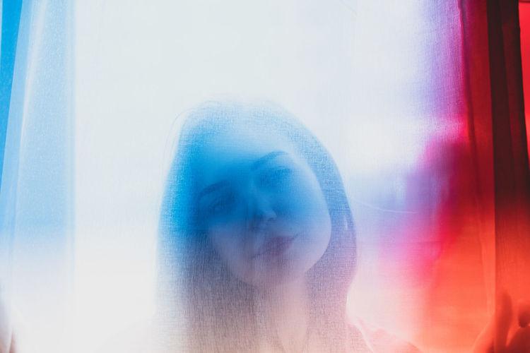Close-up portrait of woman seen through glass window
