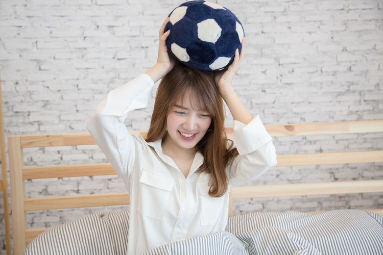Smiling Young Woman Holding Soccer Ball While Sitting On Bed At Home