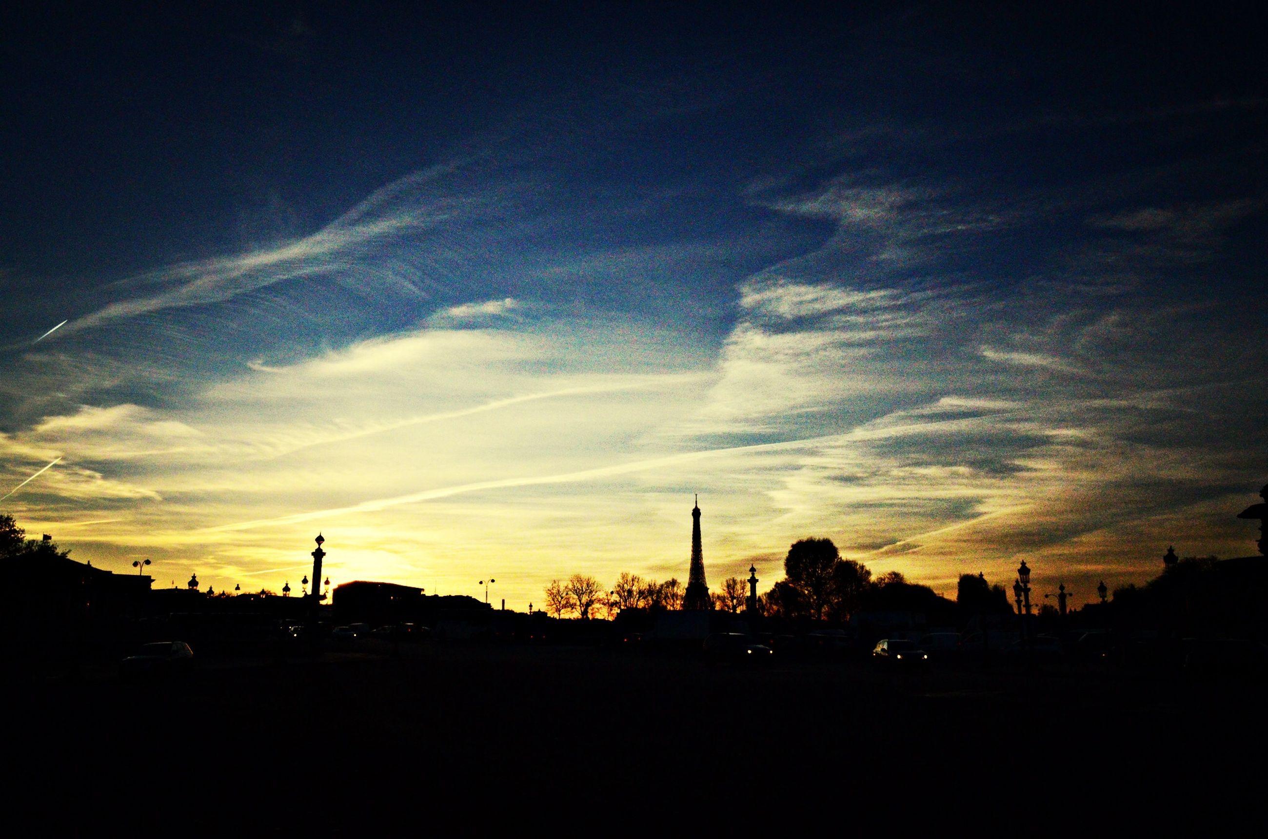 silhouette, sunset, sky, building exterior, cloud - sky, built structure, architecture, dark, cloud, road, city, street, car, street light, tree, dusk, outdoors, beauty in nature, transportation, nature