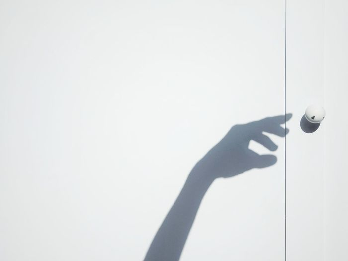Person holding umbrella against wall