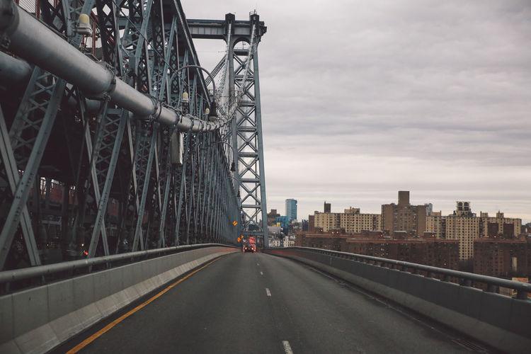 Manhattan bridge in city against cloudy sky