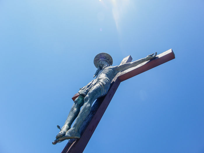 Low angle view of jesus christ on cross against clear blue sky during sunny day