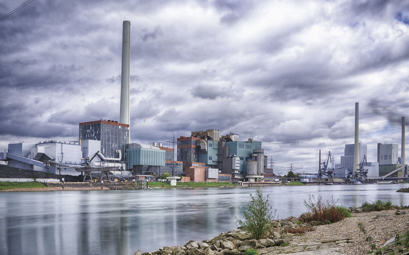 Factories by river against cloudy sky