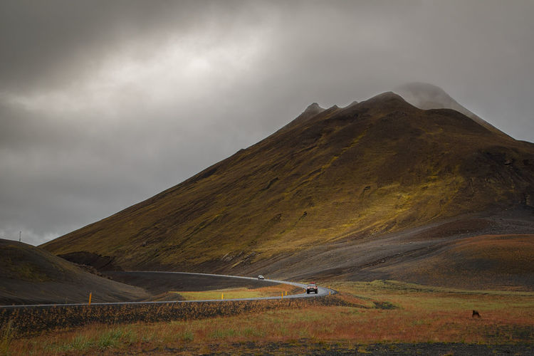Vehicle on road by mountain against sky