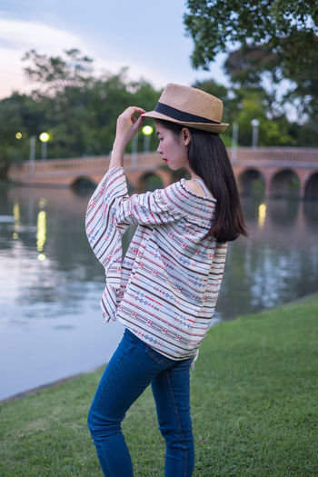 asian woman tourists. he is posing for a model fashion concept. in the park and tourist attractions. happily during travel the holidays and relax. Smile Woman Travel Asian  Landmark Picture Females Background Portrait Young Adult City Tourism Vacation Thailand person Happy Summer Outdoors Beautiful Bangkok Holiday Relax Hat Place Place Of Worship Attractions Girl Traveler Tourist Journey Technology Adventure People Lifestyles Trip Traveller Concept Nature Talking Lawn Grass Public Park Fashion Models One Person Standing Young Women Beautiful Woman Casual Clothing