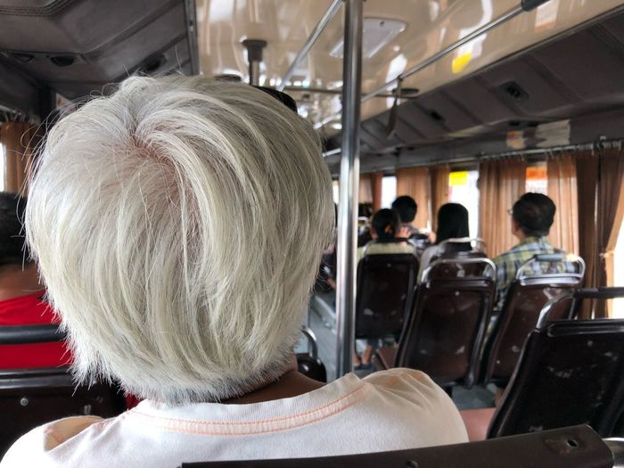 Oldie in mass transporting service. Real People Group Of People Incidental People Women Adult Rear View Indoors  Lifestyles People Men Transportation Headshot Day Mode Of Transportation Leisure Activity Focus On Foreground Seat