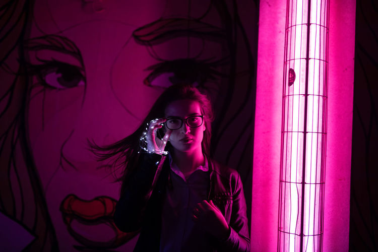 Portrait of young woman wearing eyeglasses by illuminated pink neon light