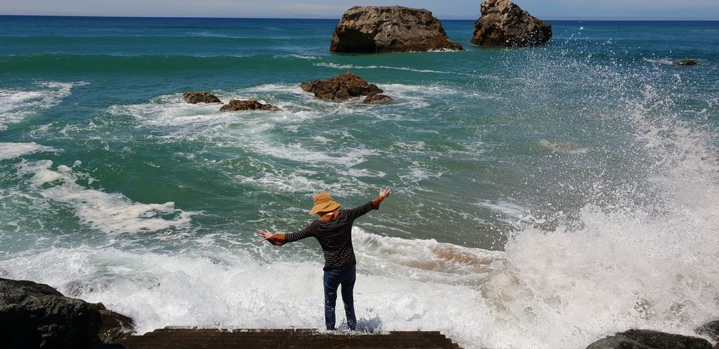 Man with arms outstretched standing in sea