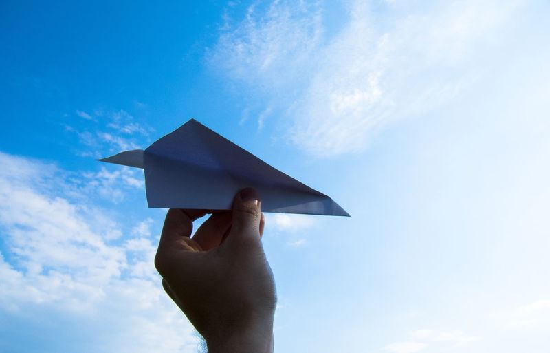Low angle view of person holding paper plane against sky