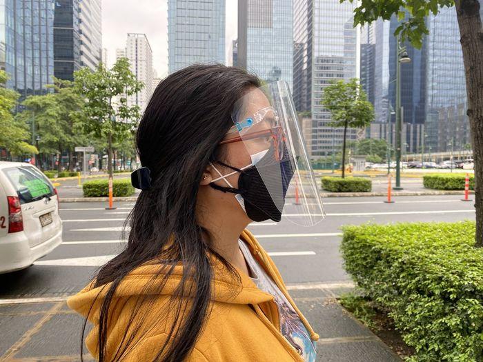 Portrait of woman with umbrella on city street