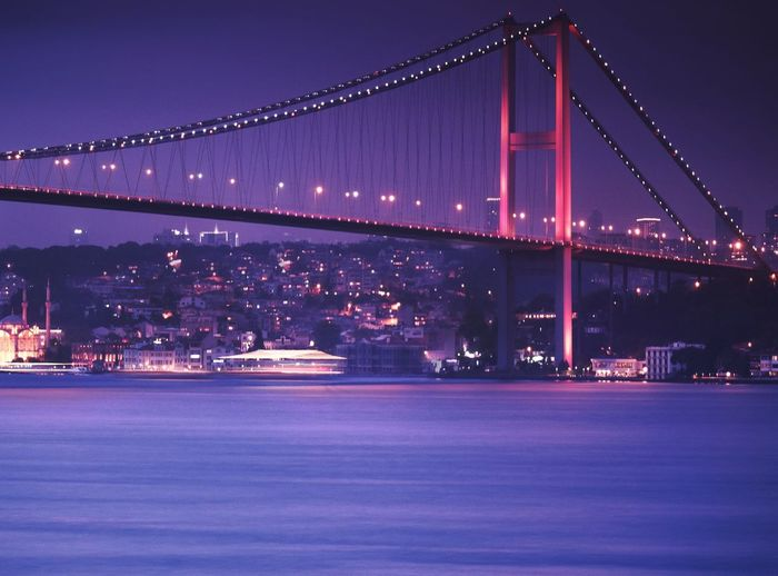 Low angle view of illuminated bosphorus bridge over river against cityscape