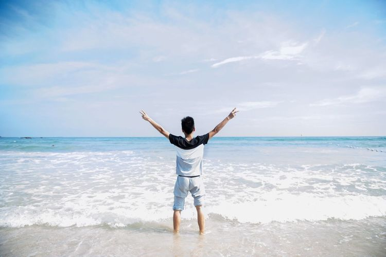 Rear view of man gesturing while standing on shore at beach against sky