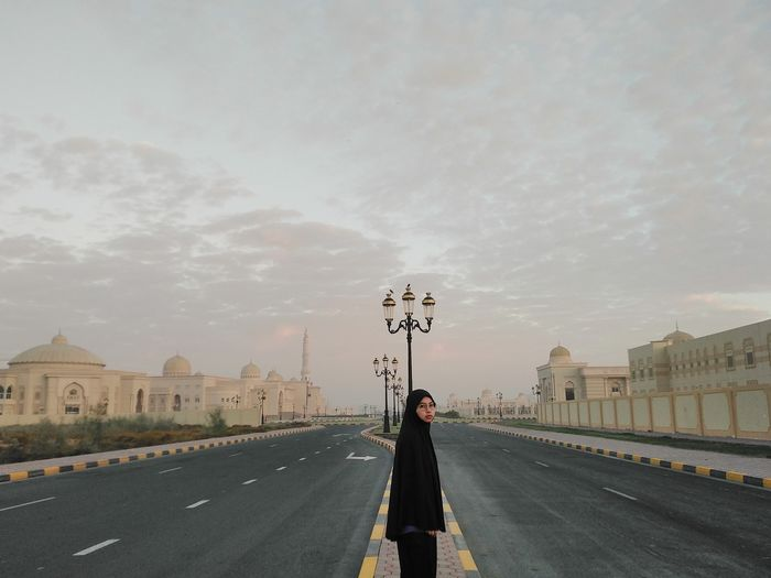 Woman standing on road in city against sky
