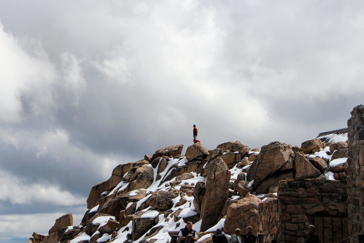 Man standing on snow covered rocks against cloudy sky