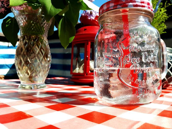 Summer table Red Checked Pattern No People Close-up Pattern Outdoors Stół Lato Vacations Summer Lunch  Glass Jar Glass Jars On The Table Terrace Tablecloth Table Red Pattern Pieces Picnic Patterns Travel Destinations Holidays Weekend Glass Mug Lunch Time!