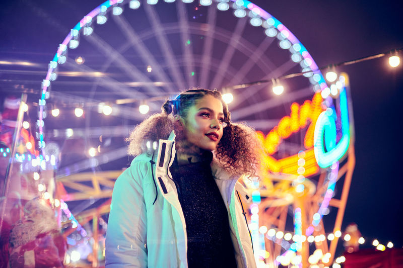 Young woman standing against illuminated carousel in amusement park