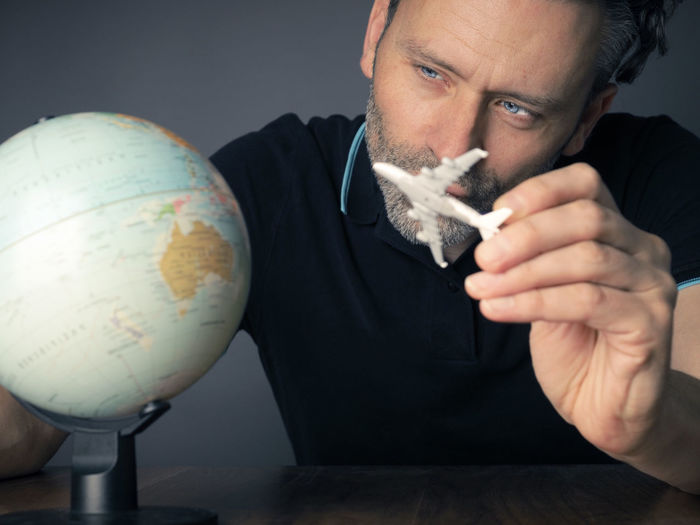 Mature man holding model airplane with globe on table