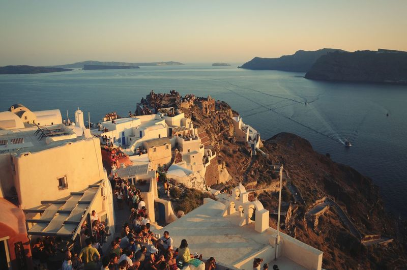 High angle view of people amidst buildings at santorini during sunset