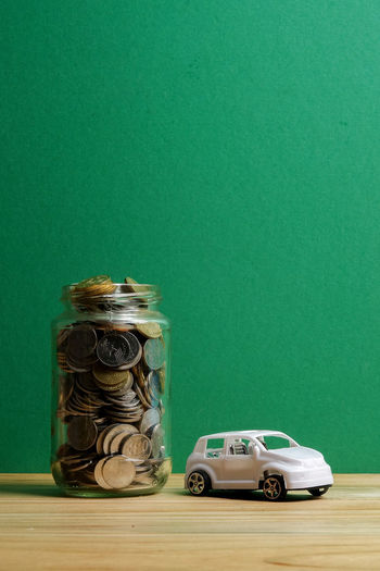 Auto Business Car Coin Colored Background Container Copy Space Finance Financing Glass - Material Green Background Green Color Indoors  Jar Large Group Of Objects Motor Vehicle No People Saving Savings Still Life Studio Shot Table Wealth