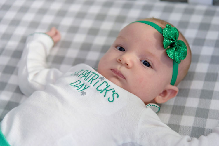 Close-up portrait of cute baby girl wearing green headband lying on bed at home