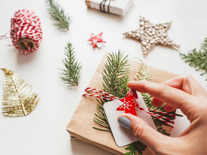Midsection of person holding christmas decoration on table