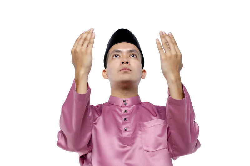 Portrait of young and handsome asian man with traditional clothing rising hand for pray over white background Studio Shot White Background One Person Indoors  Front View Portrait Young Adult Cut Out Adult Human Body Part Body Part Looking Looking Up Standing Waist Up Headshot Limb Human Arm Human Limb Purple Arms Raised