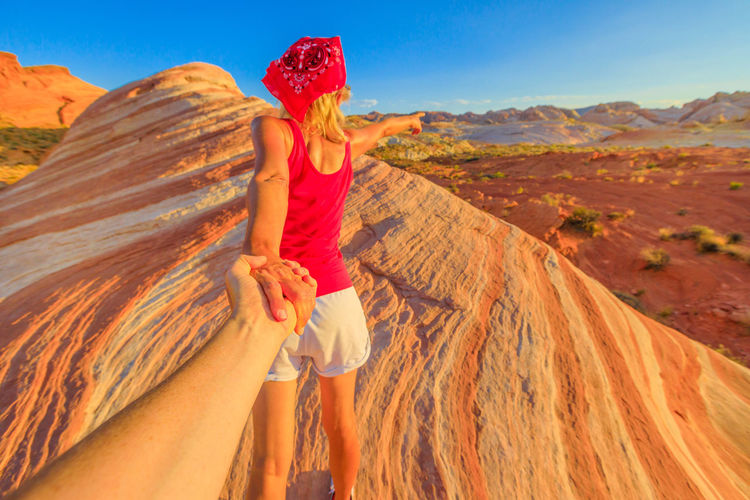 Follow me, sporty girl holding hands at top of Fire Wave Trail. Young caucasian woman in Valley of Fire State Park, Nevada, USA. Concept of the journey of woman tourist traveler, holding man by hand. Valley Of Fire Valley Of Fire State Park Valley Of Fire Nevada Nevada State Park  America American Desert Limestone Rocks Arch Natural Aerial View Panorama Road USA United States Moapa Valley Sand Valley Follow Me Gilrfriend Women Landscape Leisure Activity Two People Land Adult Sky Environment Beauty In Nature Nature Togetherness Mountain People Lifestyles Real People Scenics - Nature Day Young Women Sunlight Non-urban Scene Outdoors Positive Emotion