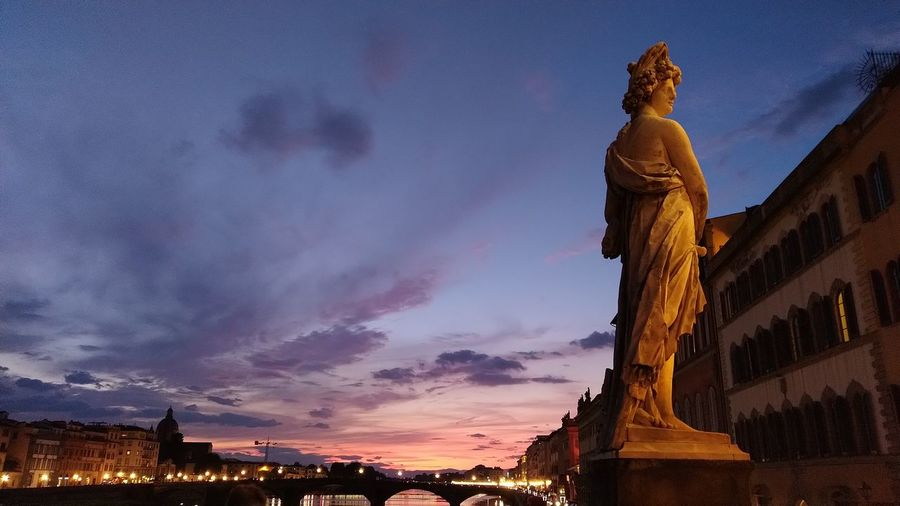 Low angle view of statue against buildings at sunset