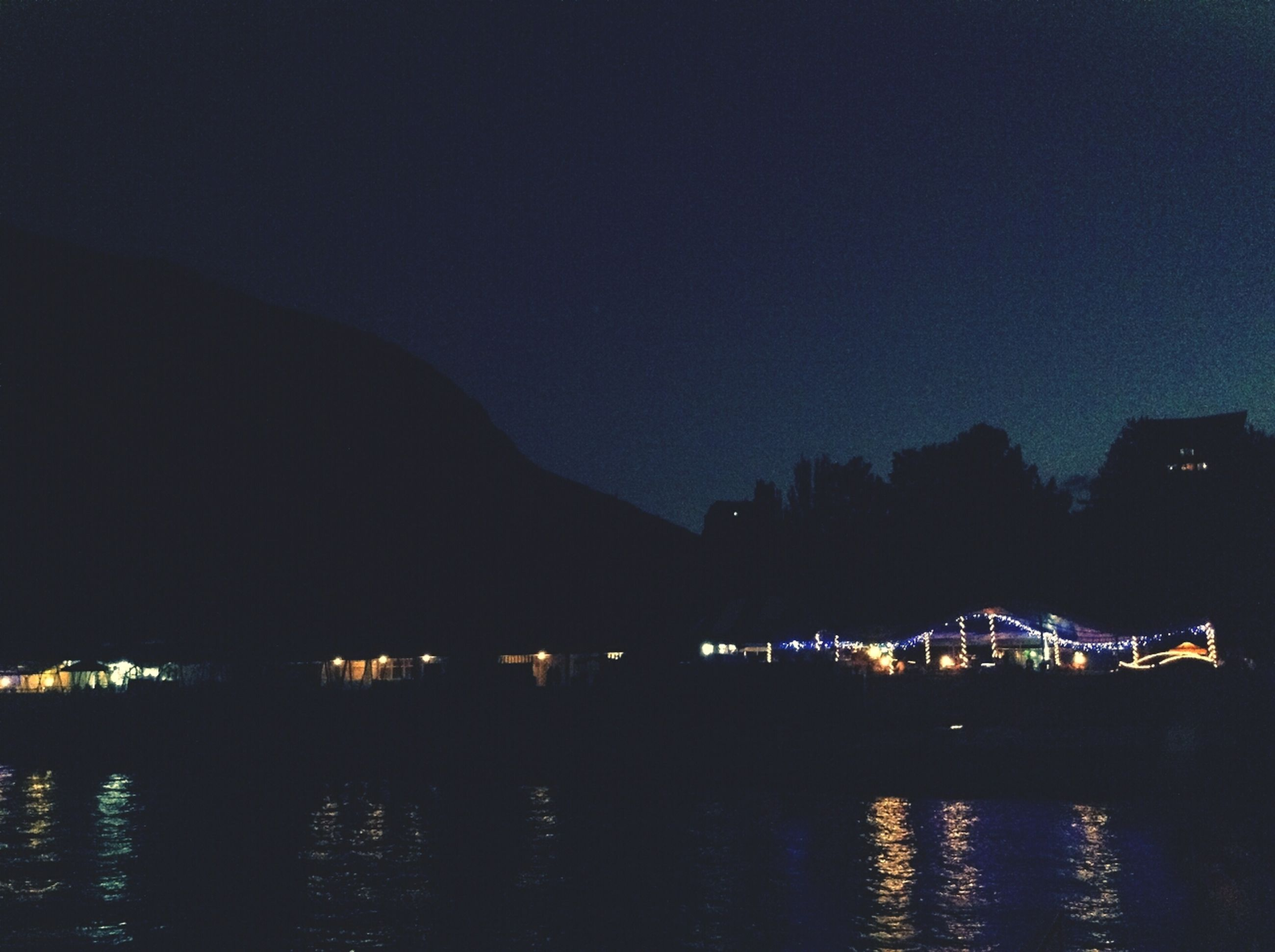 illuminated, night, water, waterfront, reflection, building exterior, built structure, river, architecture, scenics, sky, lake, tranquil scene, tranquility, beauty in nature, silhouette, mountain, dusk, nature, copy space