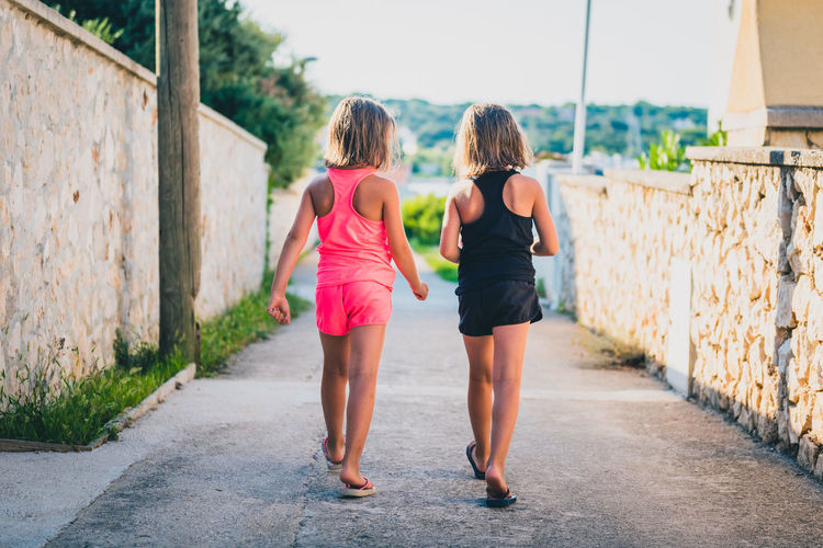 Identical twin girls sisters walking the island streets of Croatia. Children on summer vacation are waliking towards the beach through narrow Mediterranean streets of small island Silba, Croatia. Rear View Two People Real People Walking Togetherness Leisure Activity Casual Clothing Day Footpath Child Outdoors People Identical  IDENTICAL TWINS Twins Hiking Village Silba Croatia Adriatic Sea Travel Vacations Girls Flipflops Beach