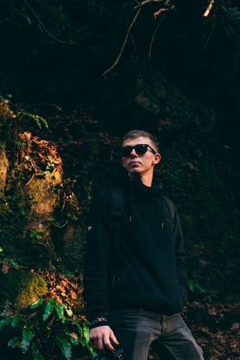 Young man wearing sunglasses standing in forest