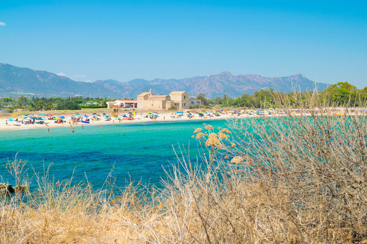 Sardinia, Italy - August 27, 2016: View of the beach of Nora, Sardinia, Italy. Ancient Architecture Bay Beach Beautiful Blue Cagliari Cap Cliff Coast Coastal Coastline Day Europe Green History Holiday Idyll Island Italian Italy Landscape Mediterranean  Nature Nora Old Palm Paradise Rock Rocky Sand Sant27efisio Sardinia Sea Seascape Season  Sky Summer Sun Sunny Tourism Tower Travel Turquoise Vacation View Watch Watchtower Water Waves