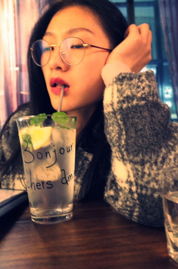 Close-up of young woman drinking drink in jar