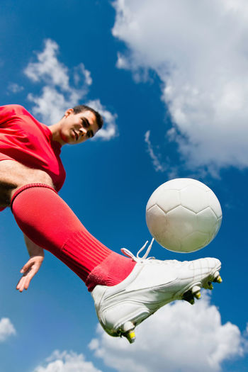 Low Angle View Of Man Playing With Soccer Ball Against Blue Sky During Sunny Day