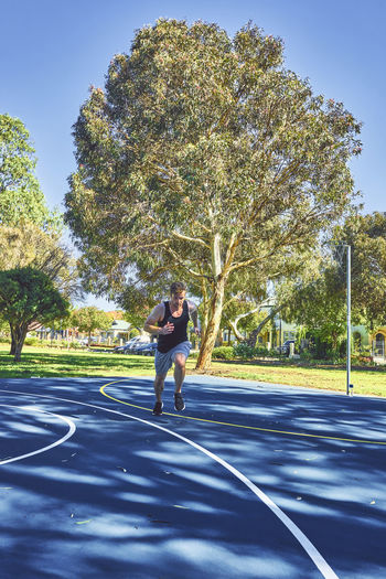 Young Man Running On Road While Exercising At Park