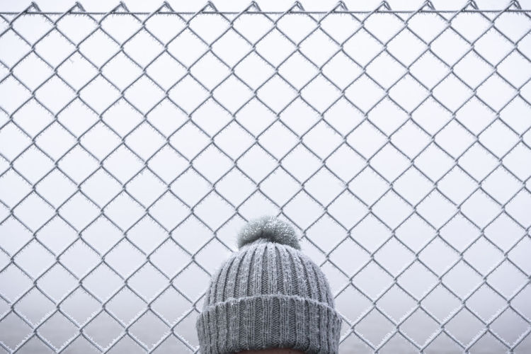 View of person head wearing knit hat standing by chainlink fence