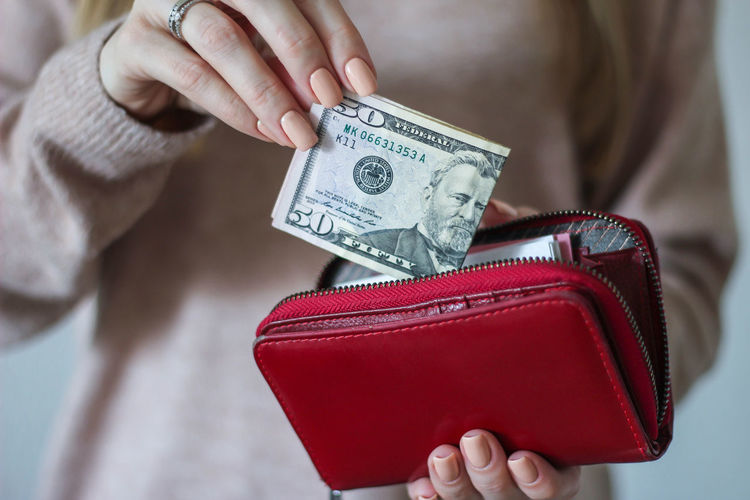 Midsection of woman holding currency and purse at home